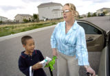 (DENVER, Colo., May 6, 2004)  Tammi Rawlins of Aurora opens the door for her son Tyler, 7, at the...