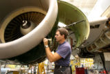 Andy Everett, cq, mechanic for Frontier Airlines, cleans seams in a inlet cowl of a Airbus engine...