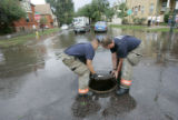 Denver firefighters Tim Robles, LEFT, and  Mark Rudolph, right, place a man hole cover at the...