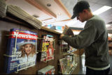 Curt Barnikel, an employee of Newsland news stand at 2200 South MOnaco Parkway, restocks a bin...