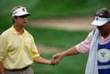 U.S. golfer David Toms takes a clean ball from his caddie on the 17th green during second round...