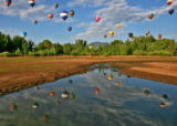 Hot air balloons taking part in the Rocky Mountain Balloon Festival are reflected in water at...