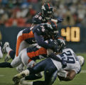 Denver Bronco's (top to bottom) Nate Webster, Michael Myers, and Nick Ferguson, take down...