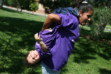 Wearing shirts with North's purple color, Santiago Lujan, 2, hangs off his sister Aliris Lujan's...