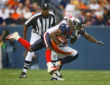 The Denver Broncos' Javon Walker (#84, WR) carries the Houston Texans' Dunta Robinson (#23, CB) on...