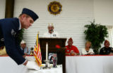 Senior Vice Commandor with Post #62 James Reiman(cq) places a U.S. flag don the table for P.O.W.s...