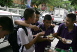 Students from the Bangkok Christian College in Thailand gather for lunch outside the school at the...