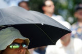 Karyn Schulman (cq) of Lakewood, Co. uses an umbrella to shade herself from the sun while watching...