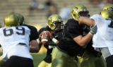 Quarterback Bernard Jackson, center, looks upfield ahead of CU's defensive line at a CU football...