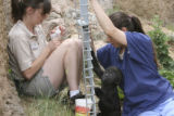 Mandy Hollingsworth, left, primate keeper, Umande, and Debbie Hegner, keeper, right, bottle feed...