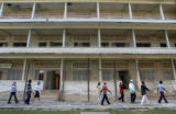 Phnom Penh, Cambodia.   November 1, 2003. Visitors to the Tuol Sleng Museum in Phnom Penh walk...