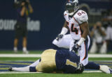 The Denver Broncos' Patrick Chukwurah (#54, DE) gets up after running into St. Louis Rams punter...
