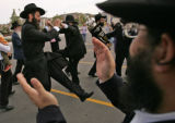Rabbi Aron Shafer (CQ), right, claps his hands as Rabbi Benjy Brackman (CQ), left, dances with...