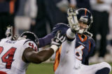 Denver Bronco's rookie quarterback Jay Cutler , right, gets knocked to the ground  in the third...