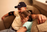 (l-r) Joe Ferand and daughter Corey, 15, watch TV on the sofa in their Aurora home Monday Aug. 28,...