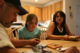 (l-r) Joe, Regina and Corey, 15, look through photos of their neighborhood post-Katrinain the...