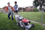 left, Tenzin Chonyi and Tenzin Dhargyal attempt to figure out the complex world of lawnmower...