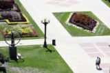 A couple walks arm in arm through the floral beauty of the park as seen from elevated position...