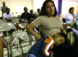 DLM01081   Antonio Rangel, 5, sleeps on his mother Claudia Rangel's lap as she listens during a...