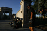 DLM03483   Police officer Ed Valerio, 62, left, stands in Civic Center Park after rousing some...