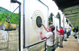 "Jim Monserud (cq), left, from Lafayette, and other participants check the targets from ""The..."