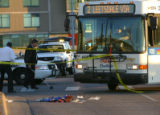 Police investigators examine the scene of a fatal RTD bus verses pedestrian collision on North...