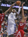 Denver Nuggets forward Carmelo Anthony, middle, drives to the basket as he splits Houston Rockets...