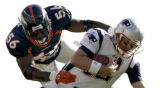 Denver Bronco's line backer, Al Wilson, left, pulls down New England Patroits' Quarter Back, Tom...