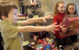 Timothy Golden, 5, stretches his arms to receive a Christmas gift from his family at The...
