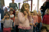Three year-old Ellie Sindler (cq, center in pink sweater) of Denver listens to one of her teachers...