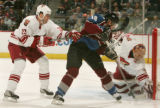 Goalie Brian Boucher saves a shot by Alex Tanguay as he is hooked by Paul Mara pf Phoenix in the...