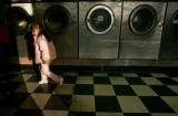 Addy Guerue (cq),3, paces up and down the isle of commercial clothe dryers while her mother does...