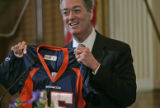 Colorado Governor Bill Owens holds up the Jersey that former Colorado Governor Roy Romer wore...