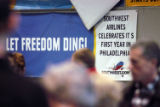 Southwest Airlines passengers pass a sign commorating one year at Philadelphia International...