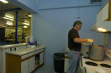 Charles Feely (cq), a resident at New Genesis, stirs soup in the shelter's kitchen Thursday,...