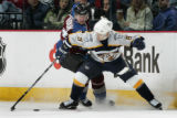 Colorado Avalanche player Milan Hejduk, left, fights for the puck with former teammate now...