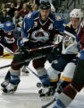 Colorado Avalanche player Rob Blake, left, fights for the puck against Nashville Predator Ryan...