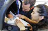Denver residents Mike and Carie Fay care for baby Josiah as they wait for their luggage at DIA...