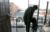 Jairo Guzman, 16, hangs out on a fire escape three stories above the gang infested streets of Los...