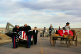 Marines prepare to transfer the casket carrying Cpl. Brett Lundstrom from a hearse to a horse...
