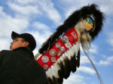 Louis Kills Straight, cq, holds a staff adorned with Bison fur, eagle feathers and plumes along...