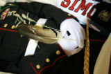 An eagle feather rests on the body of Cpl. Brett Lundtrsom during his wake services for at the...