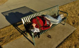 Leigh Burbank (cq), of Denver, enjoys reading a book while laying on a park bench in Sloan's Lake...