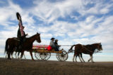 A horse drawn wagon carries the casket of Cpl. Brett Lundstrom  on the road leading to Kyle, SD,...