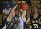 Mullen's Alex Shaw, left #15, and Grandview's Wynne Mason, middle #14, battle for possession of a...