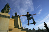 Josh Pless (cq), 16, left, does a jump of a statue while his friend David Goodman (cq), 15, right,...