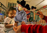 Saleah Griffin-Johnson, 21 mo., left,  of Arvada gets a visit from cowboy brothers (from 2nd to...