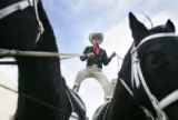 Larry Lewis (cq), of Parker, rides with one foot on each of his horses Vincent, right, and Jake,...