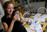 (DENVER, Colo., June 7, 2004)  April Hampshire holds her ferret, Mister Miles in front of a pile...