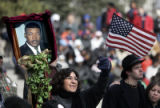 Maria Elena Alaniz (cq) from Denver carries a photo of Martin Luther King Jr. and waves a flag at...